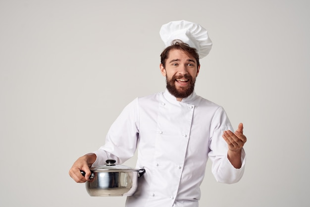 Cheerful chef with a saucepan in his hands kitchen cooking work