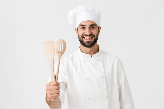 Cheerful chief man in cook uniform smiling while holding wooden kitchen utensils isolated over white wall