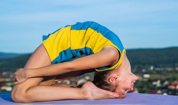 Веселый ребенок-спортсмен или гимнаст на фоне неба, растяжка.