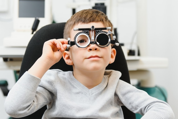 Cheerful child boy in glasses checks eye vision pediatric ophthalmologist.