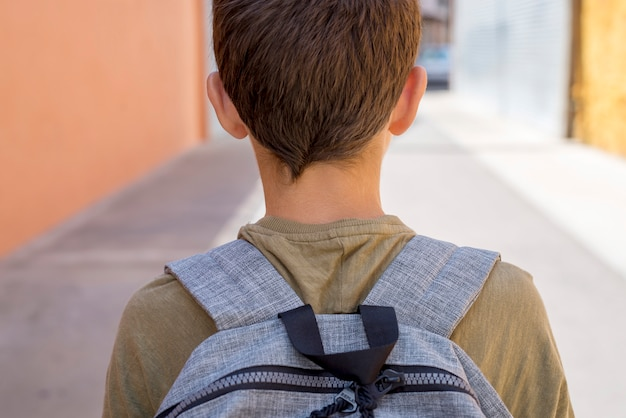 Cheerful child carrying his backpack going to the school