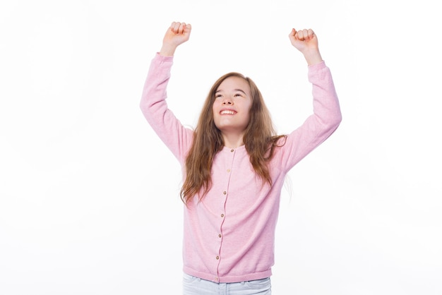 Cheerful child celebrating victory over white wall