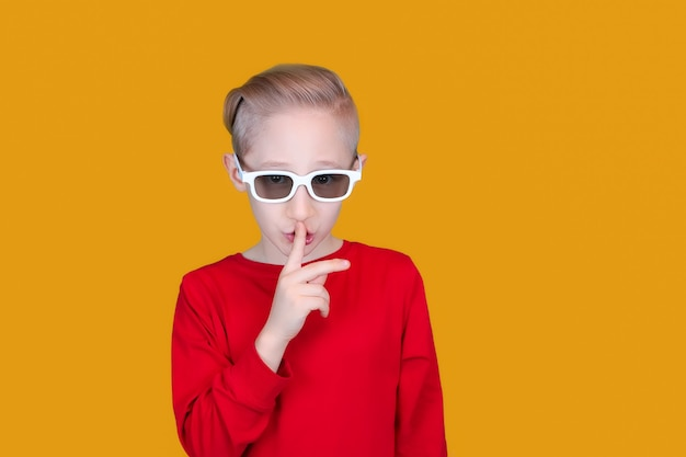 A cheerful child in children's 3d glasses puts his index finger to his lips and makes a quiet gesture