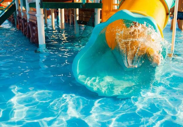 A cheerful child descends from a bright slide-tunnel into the pool and makes splashes