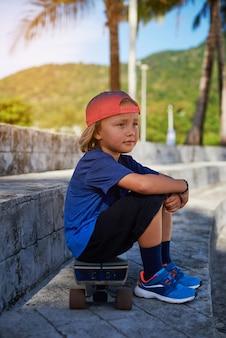 야구 모자를 쓴 운동복을 입은 쾌활한 아이가 스케이트보드에 앉아 멀리 바라보고 있습니다. 태국에서의 휴가와 휴식.
