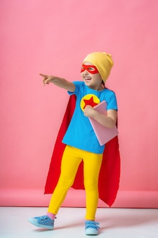 Cheerful child dressed in superhero costume and a hat with a book in his hands.