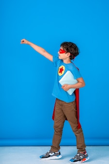 Cheerful child dressed in superhero costume hold book and stretches out his hand