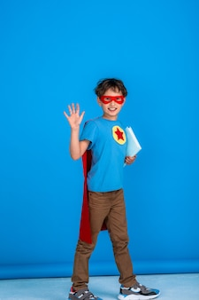 Cheerful child dressed in a superhero costume holds a book and waves.