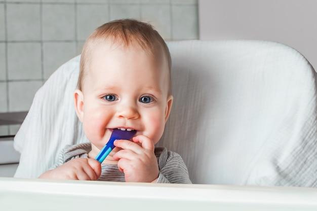 元気な子供はスプーンで食べ物を食べます。ハイチェアで幸せな少年の肖像画を閉じます。給餌