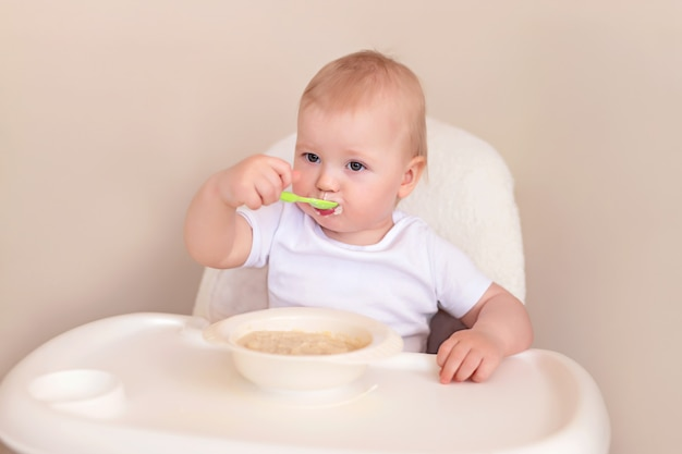 A cheerful child eats oatmeal with a spoon