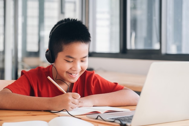 Cheerful child excited using computer for online learining. online education and self study and homeschooling concept.