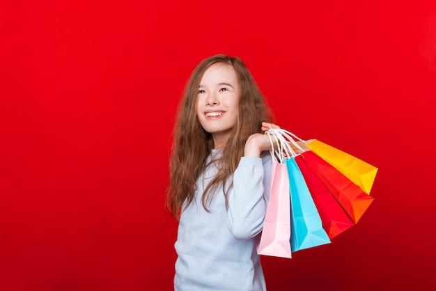 陽気な子供、買い物袋を持って赤い壁を見渡す女の子