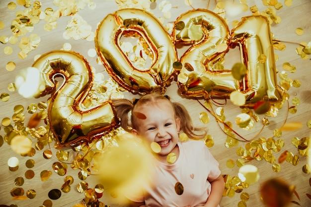 숫자 2021을 가진 쾌활한 아이 소녀는 황금색 색종이에 기뻐합니다