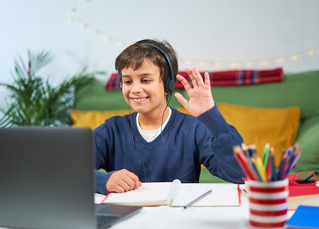 Cheerful child having video conference on laptop with teacher from home, wearing headphones and waving on screen, free space
