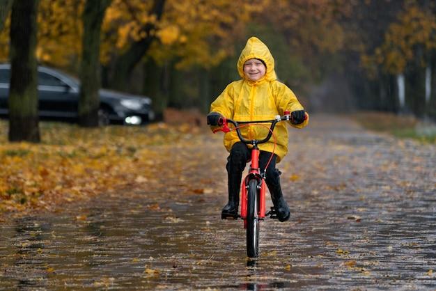Веселый ребенок в желтом плаще катается на велосипеде в осеннем парке. мальчик едет по аллее в дождливом парке.