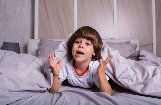 A cheerful child in pajamas is lying on cotton bed linen on a bed
