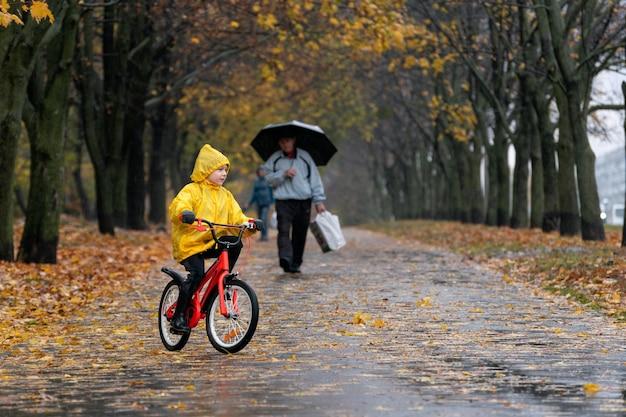 Веселый ребенок, езда на велосипеде в парке под дождем. мальчик в желтом плаще едет на велосипеде по мокрой аллее.
