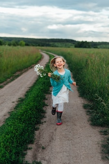 A cheerful child runs with a bouquet of daisies in boots