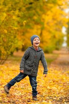Веселый ребенок улыбается в желто-золотом осеннем лесу