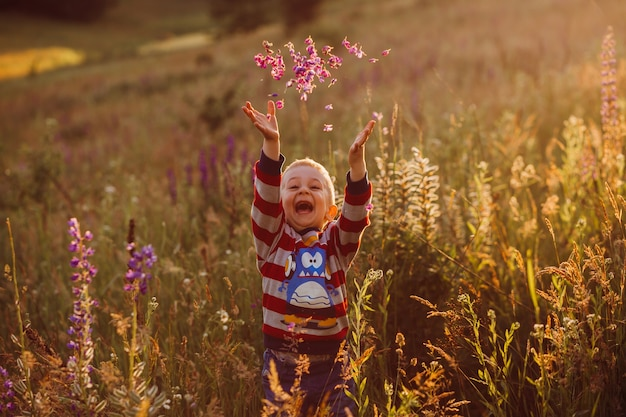 Cheerful child throws petals up posing on the field of lavander