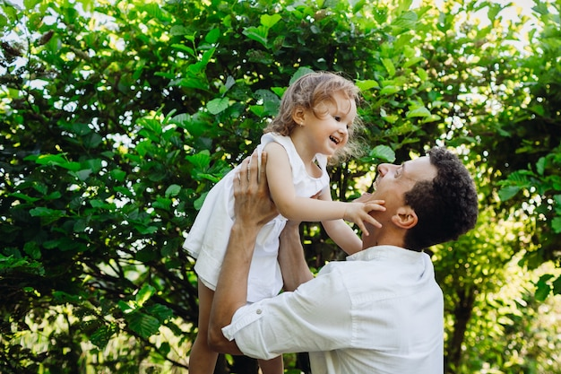 Cheerful child touches father's face while they pose in green forest