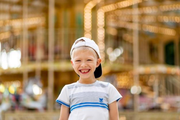 Веселый ребенок гуляет в парке развлечений