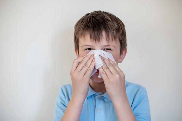 Cheerful child wipes nose white handkerchief. nose hygiene. child with flu or cold protected from viruses among patients with coronavirus