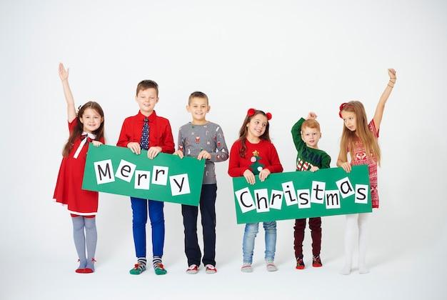 クリスマスの装飾を保持している陽気な子供たち