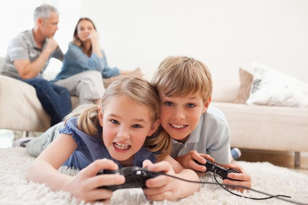 Cheerful children playing video games with their parents on the