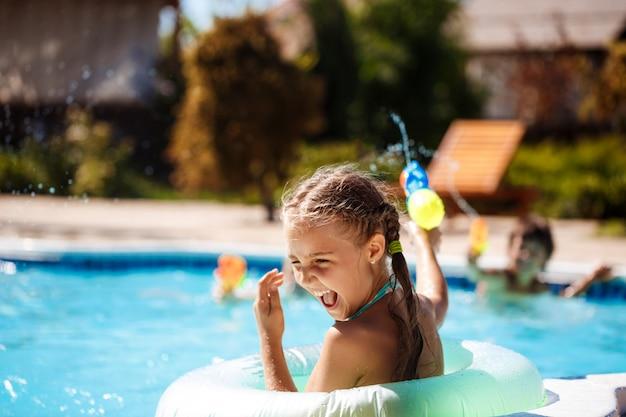 Веселые дети играют в водяные ружья, радуются, прыгают, купаются в бассейне.