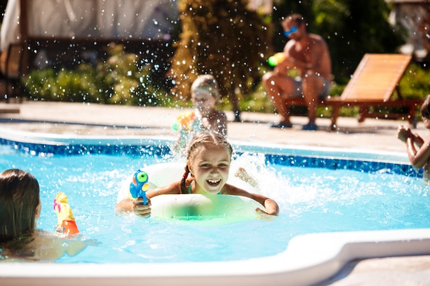 Cheerful children playing waterguns, rejoicing, jumping, swimming in pool.