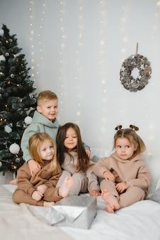 Веселые дети с подарками рядом с елкой