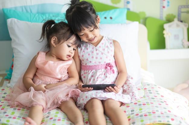 遊んで手でスマートフォンを持つ陽気な子供たち