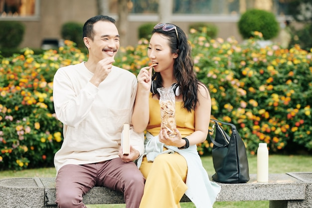 Cheerful chinese boyfriend and girflriend sitting on bench, talking and eating delicious snacks when enjoying romantic date