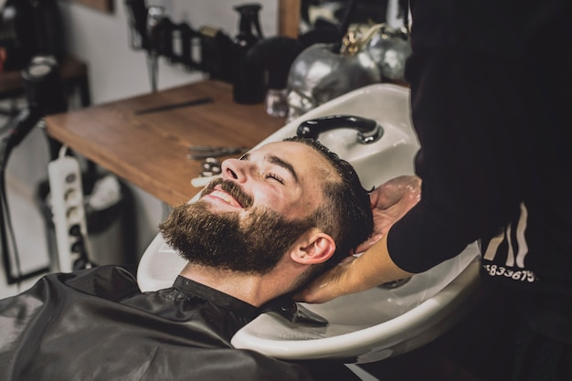 Cheerful client washing head in salon