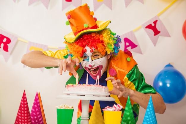 케이크와 함께 휴가에 쾌활 한 광대 소년