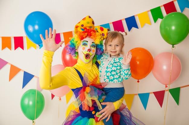 Веселый клоун с малышом на красочной вечеринке