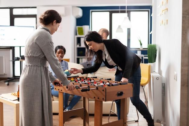 Cheerful colleagues enjoying game at foosball table