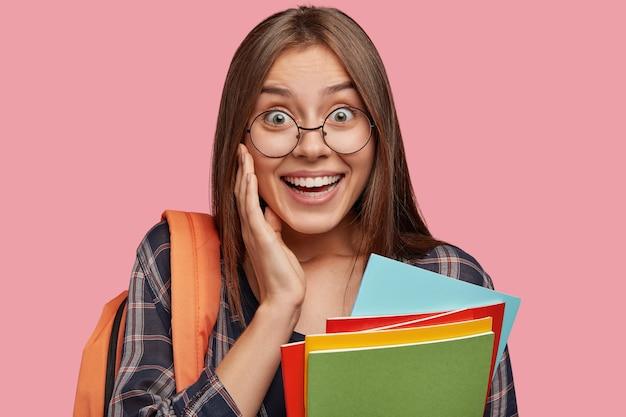 Allegro studente di college in posa contro il muro rosa con gli occhiali