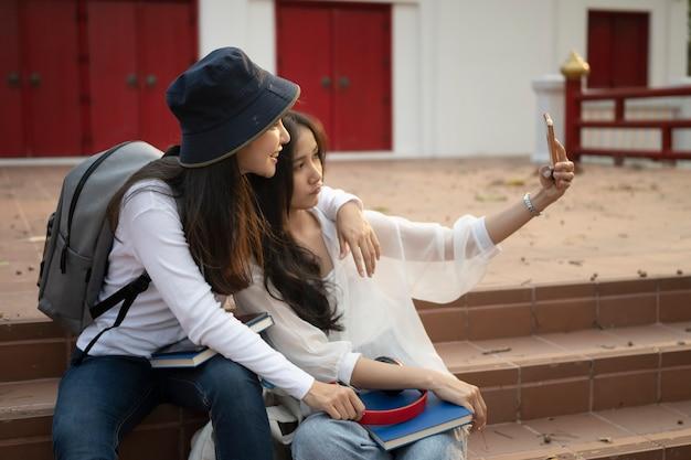 元気な大学生が授業の後に楽しみ、大学のキャンパスで自撮りをしている。