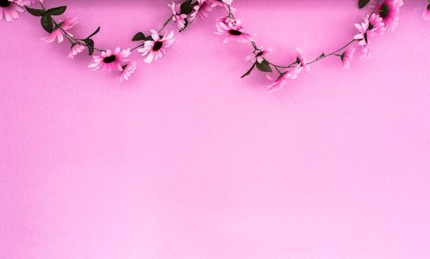 ピンクの壁の背景のテクスチャにぶら下がっている陽気なカラフルなピンクパープルデイジーガーランド美しい
