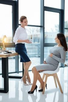 Веселое общение. довольные друзья в полном объеме разговаривают во время увлекательной работы в офисе.