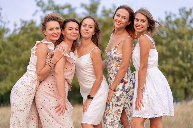 A cheerful company of beautiful girls friends enjoy the company and have fun together in a picturesque place of green hills.