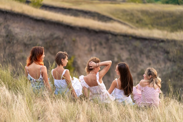 A cheerful company of beautiful girls friends enjoy a picturesque panorama of the green hills at sunset