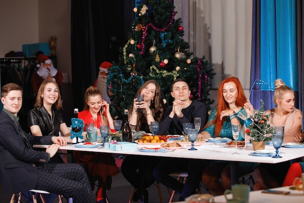 Cheerful company of friends celebrates the new year at a table near the christmas tree with garlands. women and men laugh, rejoice with champagne glasses.