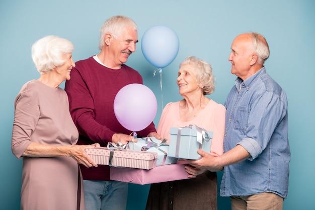 Веселая компания дружных пенсионеров с воздушными шарами и подарочными коробками отмечает праздник или юбилей.