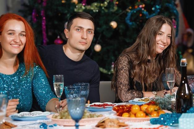 陽気な友達の仲間が、花輪のあるクリスマスツリーの近くのテーブルで新年を祝います。女性も男性も笑い、シャンパングラスで喜ぶ。