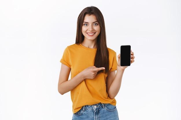 노란색 티셔츠를 입은 쾌활하고 자신감 있는 매력적인 브루네트 소녀, 스마트폰을 들고, 모바일 화면을 가리키며 웃고, 멋진 전화 응용 프로그램을 추천하고, 프로모션 코드에 대한 링크를 제공하고, 경품