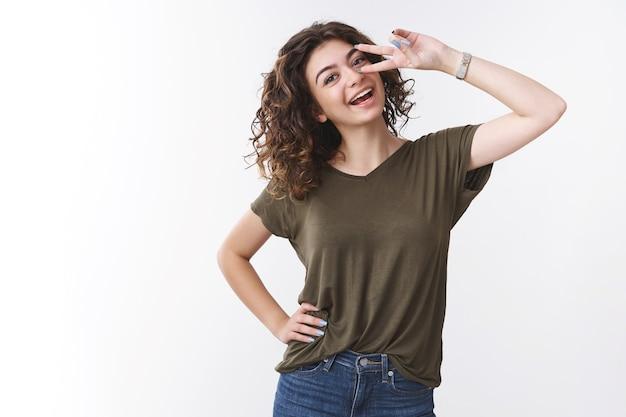 陽気で自信に満ちた格好良い若い女性は、休日の応援を楽しんでいます幸運な明るいショーの勝利または平和のジェスチャーを傾ける頭をゆったりと笑って広く白い歯、スタジオの背景