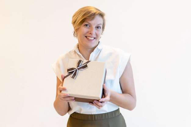 Cheerful confident mature businesswoman holding gift box